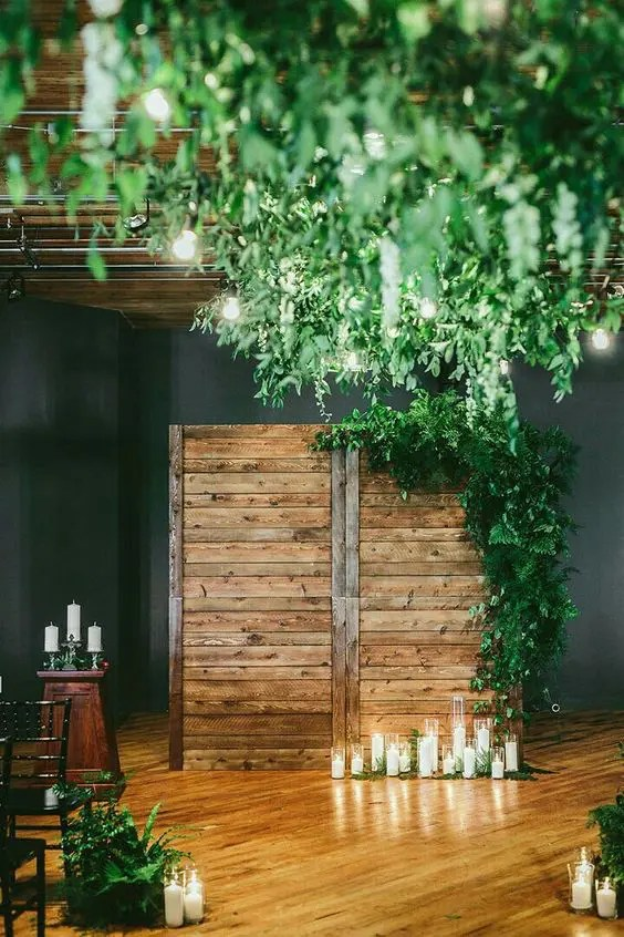 a reclaimed wood backdrop with cnaldes and lots of greenery on its corner