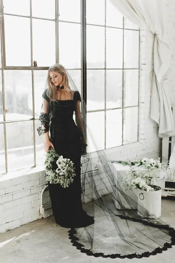 gorgeous hairstyle with a black veil with a lace trim paired with a black dress for a Halloween bride