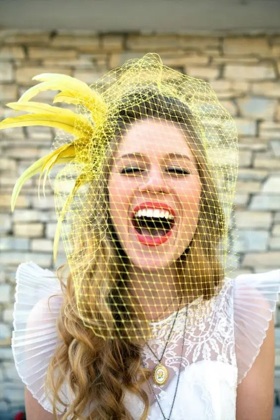 a bold yellow birdcage veil with feathers is a gorgeous idea to add fun to your look