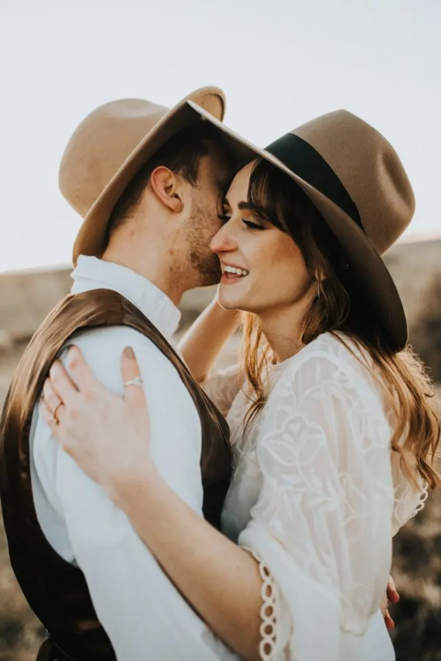 both the bride and the groom are wearing matching hats to unify their looks a little bit