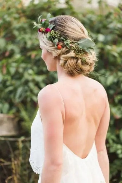 braids woven into a bun and finished with a floral crown of eucalyptus and little blooms