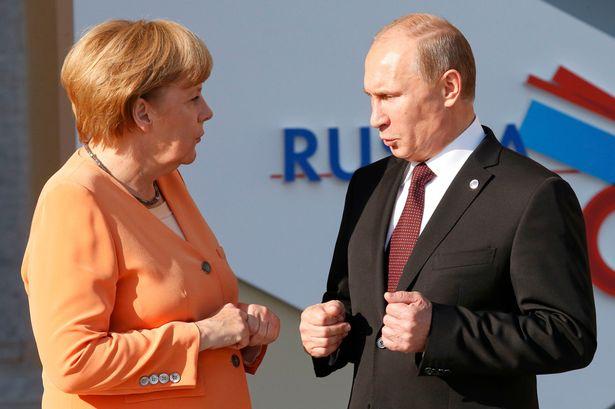 Russia's President Vladimir Putin (R) speaks with German Chancellor Angela Merkel