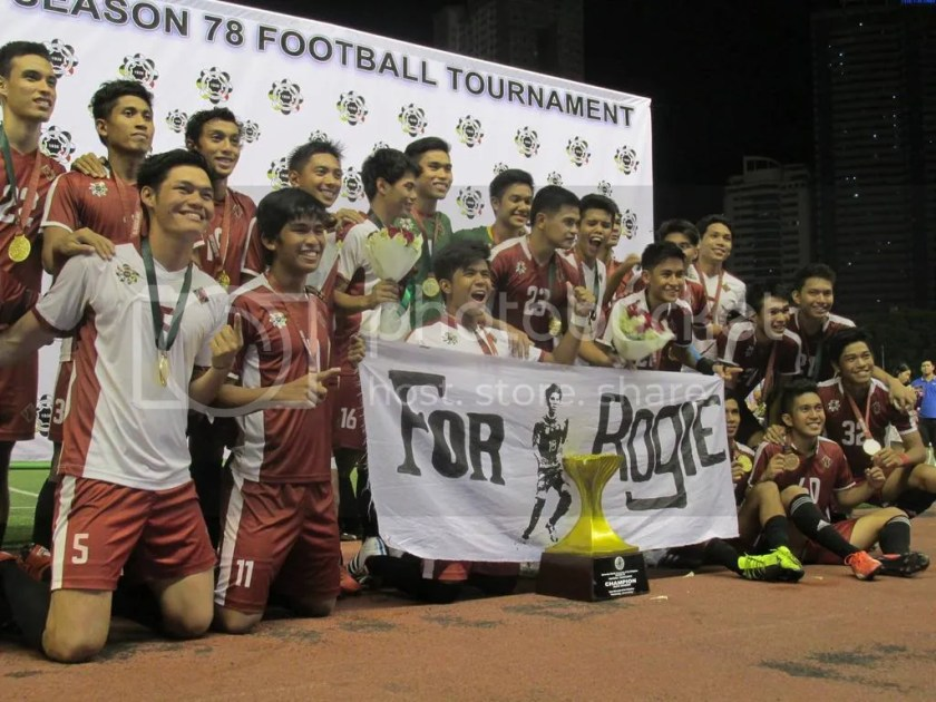 The members of the UP Men's Football Team hold a banner commemorating their fallen brother, Rogie Maglinas, after their win in the UAAP Season 78 Men's Football Tournament. Photo by David Tristan Yumol