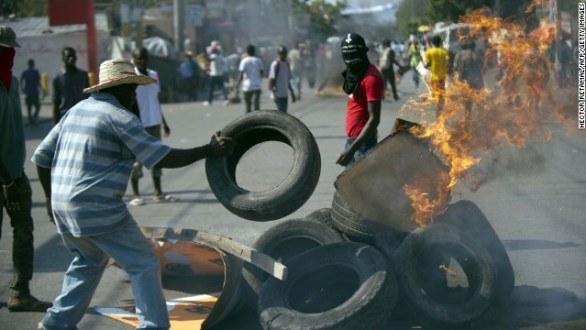 Demonstrators burn tires during anti-government protests in Port-au-Prince on December 13.