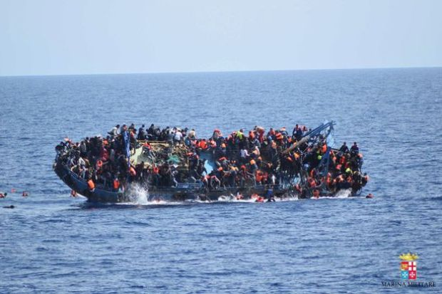 """Migrants are seen on a capsizing boat before a rescue operation by Italian navy ships """"Bettica"""" and """"Bergamini"""" (unseen) off the coast of Libya in this handout picture released by the Italian Marina Militare on May 25, 2016."""