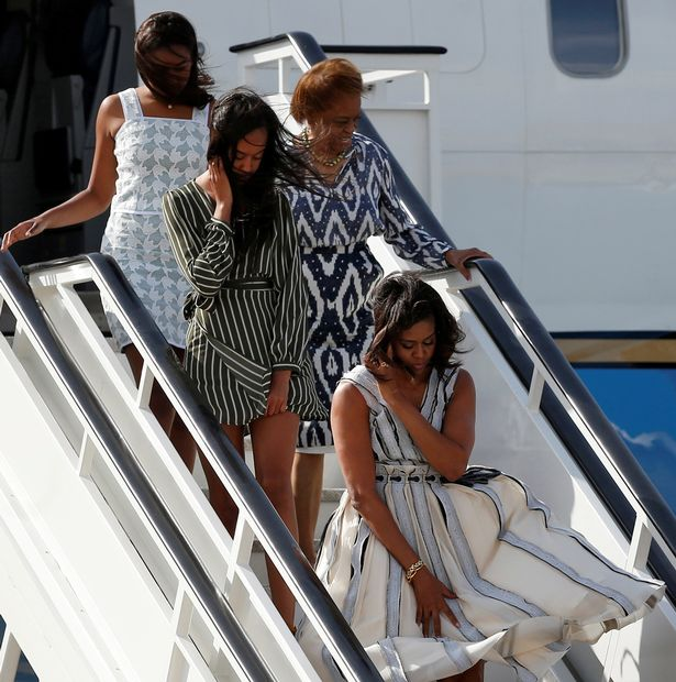 Michelle Obama tries to control her dress as she steps off her plane with her daughters Sasha and Malia and mother Marian Robinson