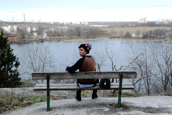 Bryanboy sitting on a wooden bench in Skansen