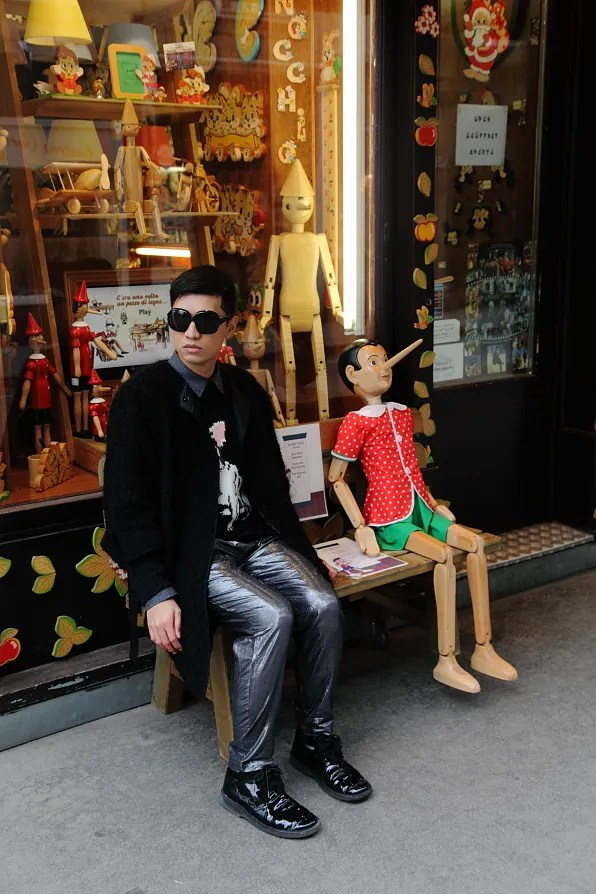 Bryanboy sitting outside a store selling pinocchio dolls