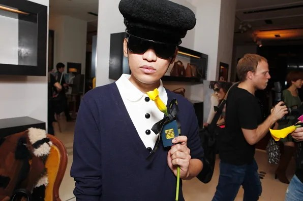 Bryanboy holding a yellow flower inside Fendi Tokyo