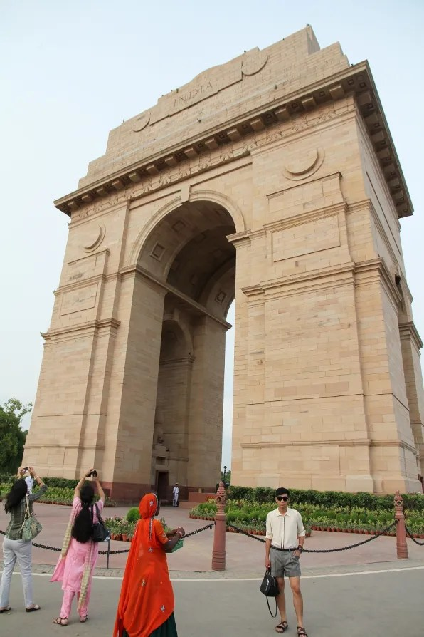 People and Indian tourists walking around India Gate