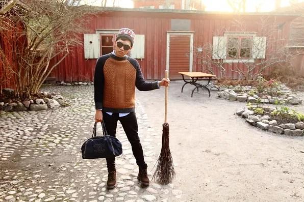 Bryanboy holding a broomstick in Skansen