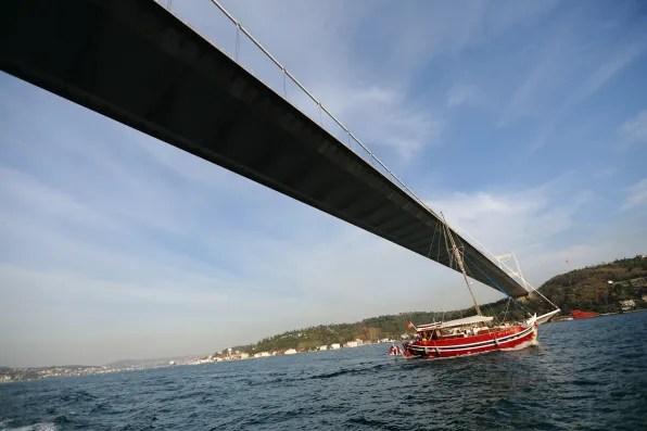 Red boat underneath Bosphorus Bridge, Istanbul