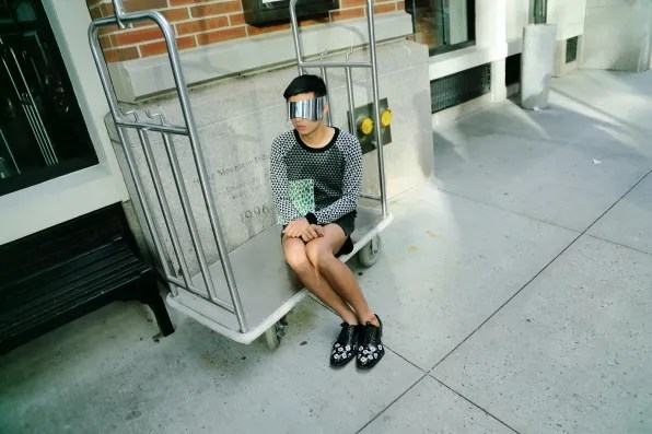 Bryanboy sitting on a luggage cart outside Soho Grand Hotel, New York