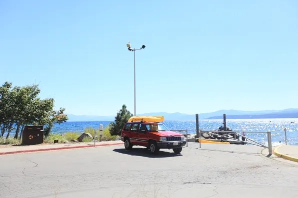 Yellow kayak on top of a car in Lake Tahoe