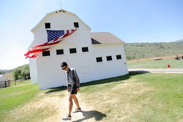 Bryanboy in front of a barnhouse with an American flag in Utah