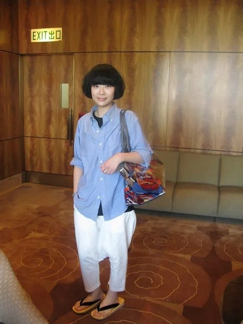 Jackie of Ming Pao Weekly carrying an Issey Miyake Pleats Please tote bag.