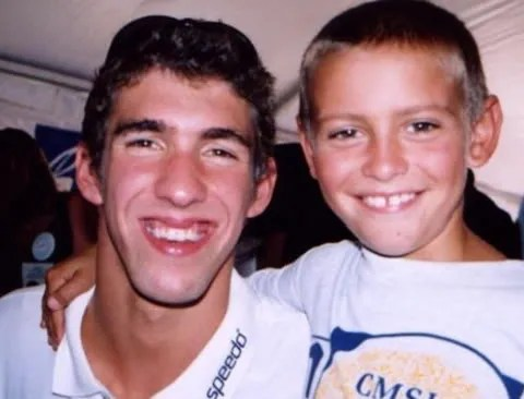 Michael Phelps with ugly teeth, posing with a fan.