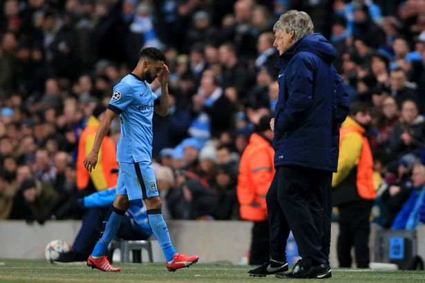 Manchester City's Gael Clichy walks past manager Manuel Pellegrini after being shown a red card