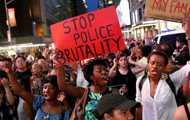 Activists protest in Times Square in response to the recent fatal shootings of two black men by police