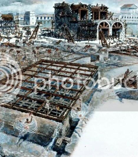 沉箱法,沉箱被拖曳至施工場地,灌滿水泥,其上鋪砌石塊