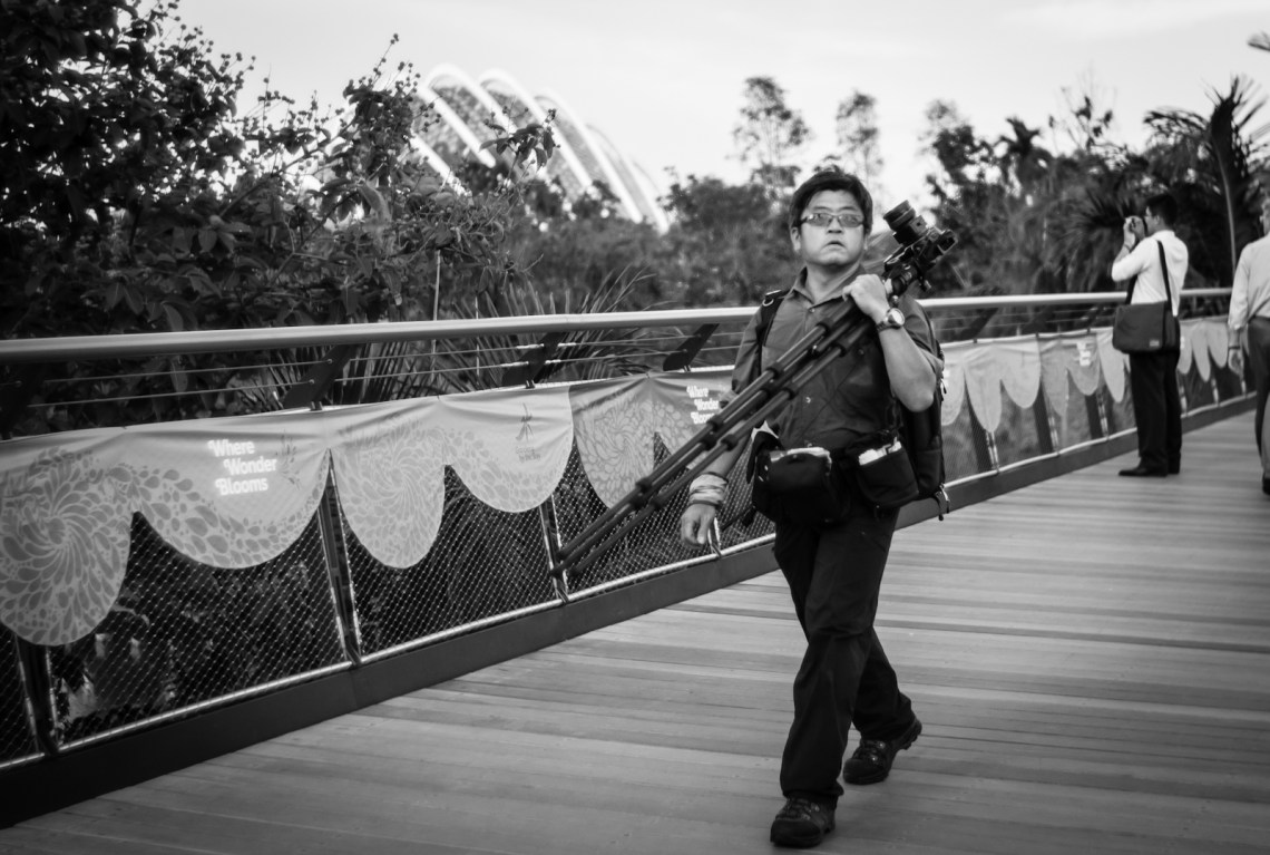 Photographer walking on a bridge
