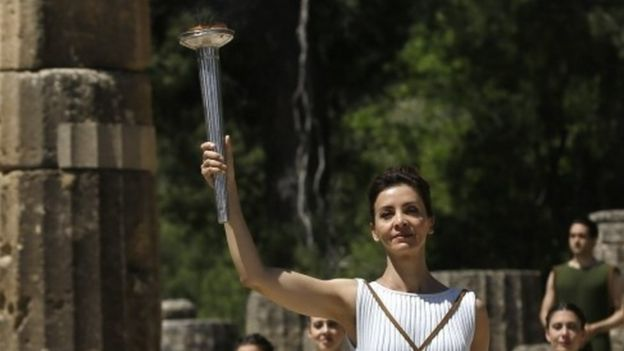 An actor dressed as priestesses with the lit Olympic flame in the ancient Olympic stadium in Greece (21 April 2016)