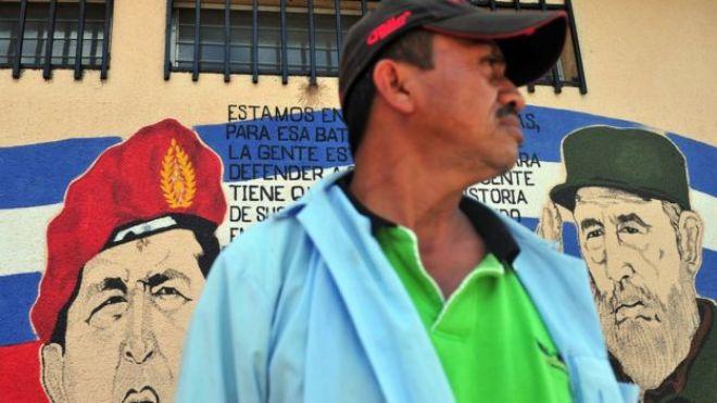 Un hombre frente a un mural con los rostros de Hugo Chávez y Fidel Castro en Nicaragua.