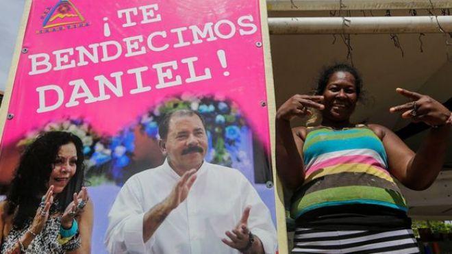 Una mujer junto a un cartel en apoyo a Daniel Ortega
