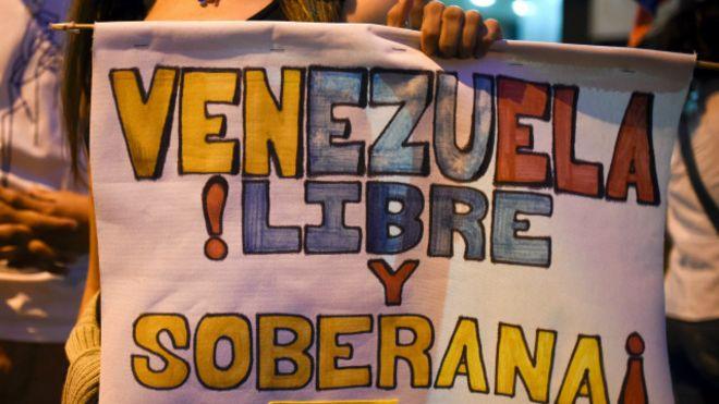 """Una joven con un poster sobre Venezuela que lee: """"libre y soberana"""""""