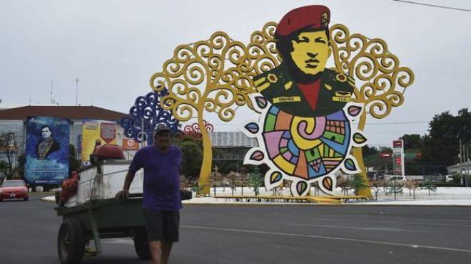 Un hombre con un carretón pasa cerca del monumento a Chávez en Managua