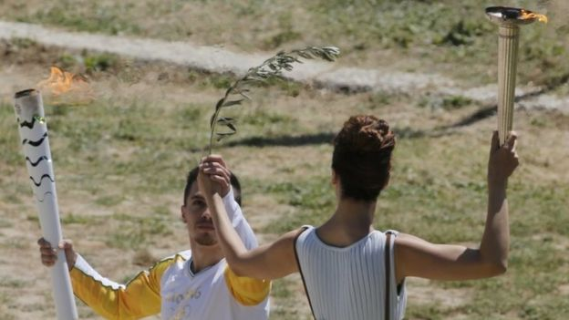 Greek actress Katerina Lehou, playing the role of High Priestess, passes the Olympic flame to the first torch bearer, Greek gymnast Eleftherios Petrounias (21 April 2016)