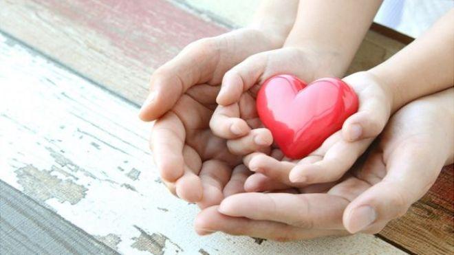 Las manos de un adulto y un un niño sosteniendo la figura de un corazón.