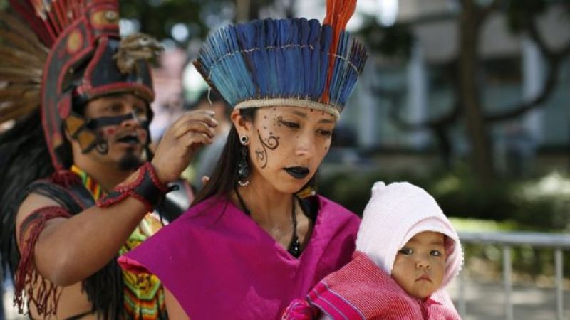 Woman holds baby as she is helped into her costume for start of Day of the Dead parade along Mexico City's main Reforma Avenue, Saturday, Oct 29, 2016