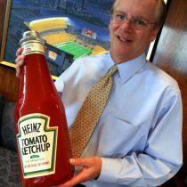 El director de Heinz William R. Johnson sosteniendo una botella enorme de ketchup