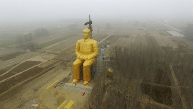 The statue, surrounded by fields