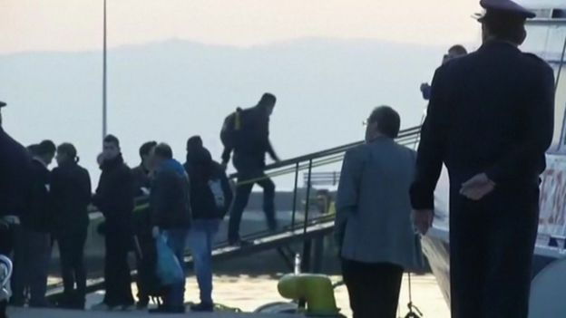 Migrants and Greek security forces at the Greek island of Lesbos