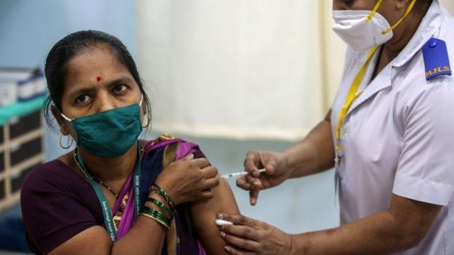 Mujer siendo vacunada en India
