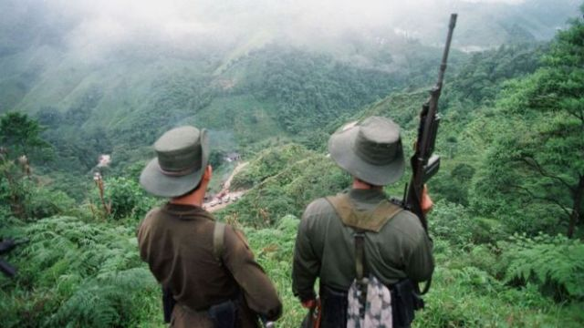 Undated picture of two armed Farc rebels monitoring the Berlin pass