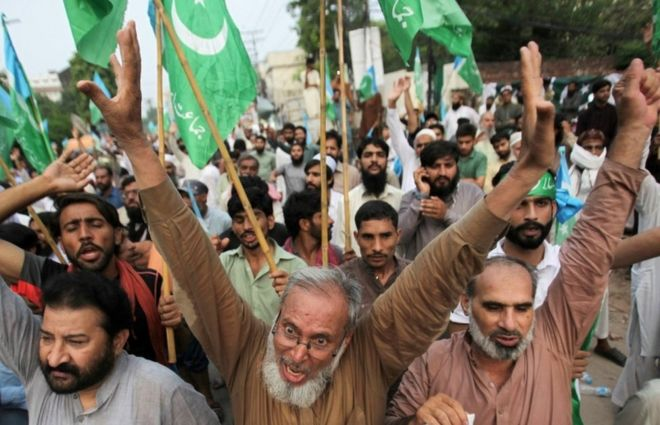 Pakistani men in Lahore chant slogans at a rally expressing solidarity with the people of Kashmir