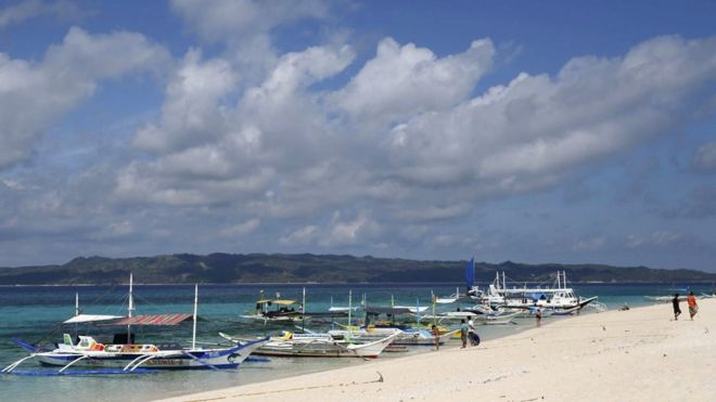 Philippines to temporarily close popular tourist island Boracay     Traditional boats line up the shore in a secluded beach on the island of  Boracay