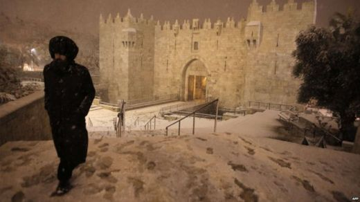 An ultra-Orthodox Jewish man walks near Damascus Gate in Jerusalems Old City as snow falls