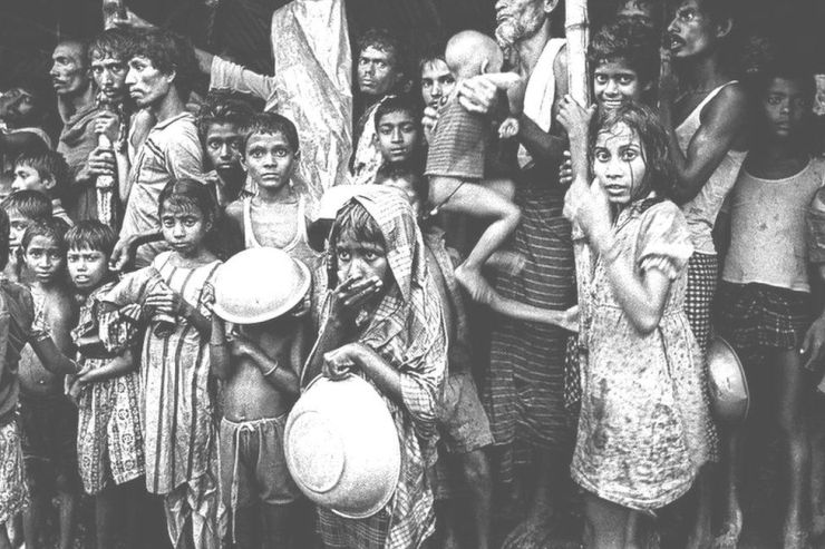 Children and adults sheltering from rain, flood victims in Mymensingh, Bangladesh. 1988.