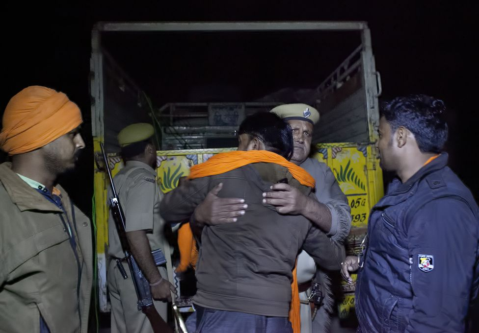 A policeman embraces Nawal Kishore Sharma after his group chases down a lorry in November 2015
