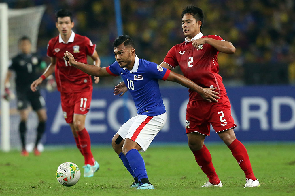 KUALA LUMPUR, MALAYSIA - DECEMBER 20: Perapat Nortechaiya of Thailand challenges Safee Sali of Malaysia during the 2014 AFF Suzuki Cup 2nd leg final match between Malaysia and Thailand at Bukit Jalil National Stadium on December 20, 2014 in Kuala Lumpur, Malaysia.  (Photo by Stanley Chou/Getty Images)