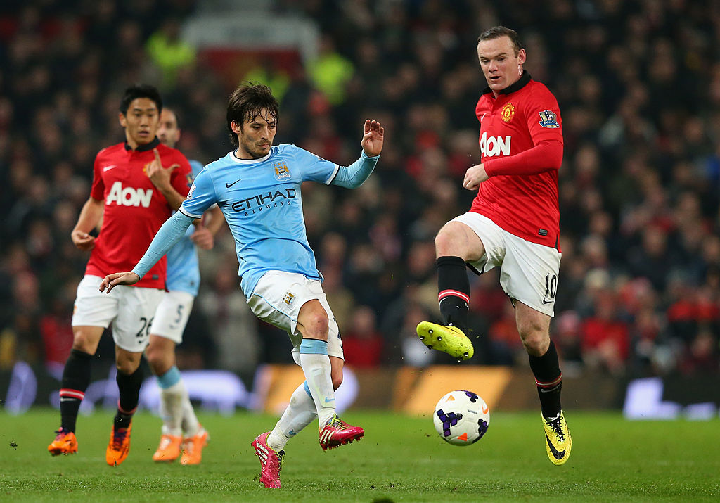 MANCHESTER, ENGLAND - MARCH 25:  David Silva of Manchester City competes with Wayne Rooney of Manchester United during the Barclays Premier League match between Manchester United and Manchester City at Old Trafford on March 25, 2014 in Manchester, England.  (Photo by Alex Livesey/Getty Images)