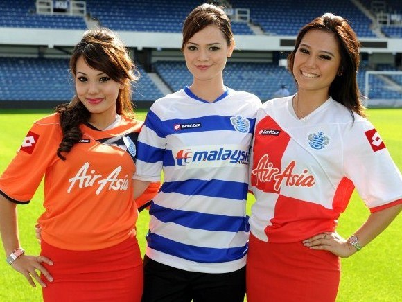 Airline stewardesses from Malaysian Airlines and Air Asia wearing the new club kit