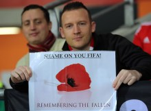 "CARDIFF, WALES - NOVEMBER 12: A Wales fan with a ""Shame on you FIFA"" about the football governing body's decision not to allow home teams to wear the poppy during the 2018 FIFA World Cup Qualifier between Wales and Serbia at the Cardiff City Stadium on November 12, 2016 in Cardiff, Wales. (Photo by Athena Pictures/Getty Images)"