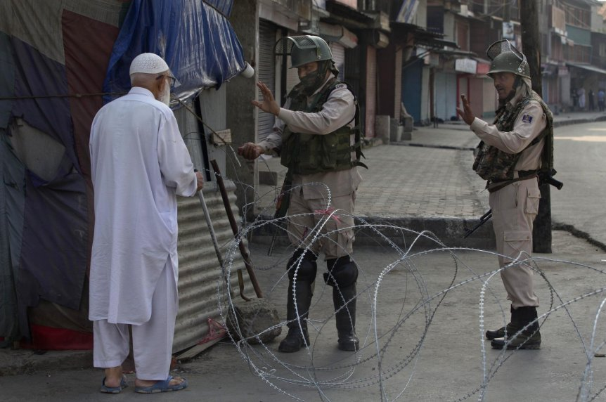An elderly Kashmiri man is stopped before being allowed to pass near a temporary checkpoint set up by Indian paramilitary soldiers during a lockdown in Srinagar, Indian-administered Kashmir, Aug. 23, 2019. (AP Photo)