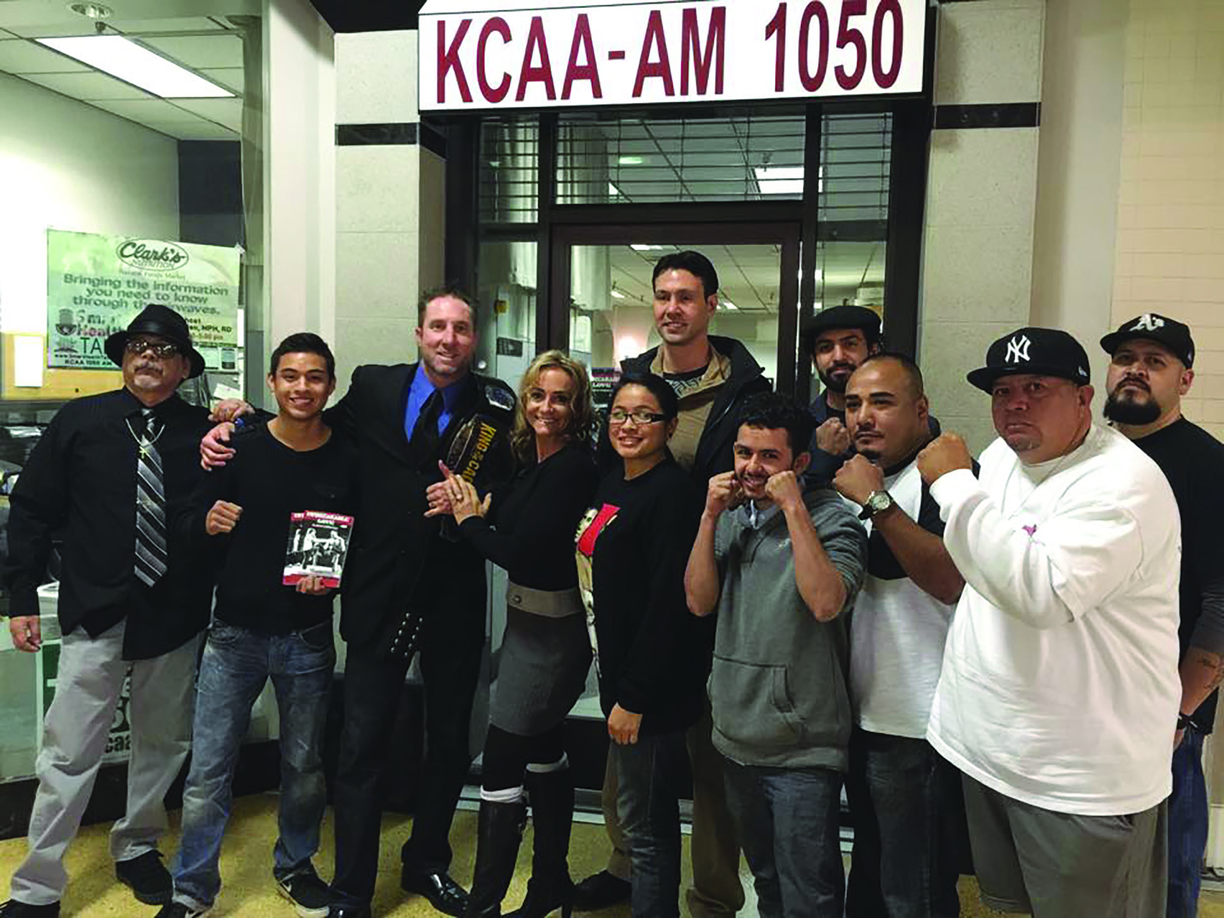 Members of the PAL Boxing Gym in Colton take a photo with MMA fighter Brian Warren (left with belt) and KCAA AM 1050 Radio Special Events Manager Danny Alcaraz (far left)