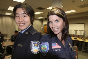 Photo/Ricardo Tomboc  Shanghai Police College Student Lizzie Chen and Forensic Student Rebecca Meyer stand side by side/shoulder to shoulder displaying their departments patches.